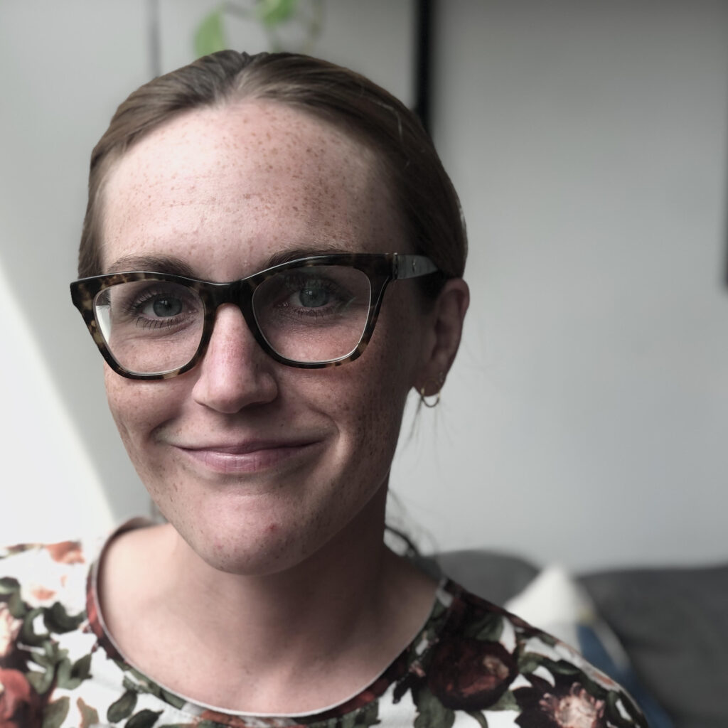 Lisanne, a fair-skinned woman with hair pulled back and tied up is smiling directly into the camera. The background is blurred. Lisanne is wearing a shirt with flowers and cat-eye glasses.