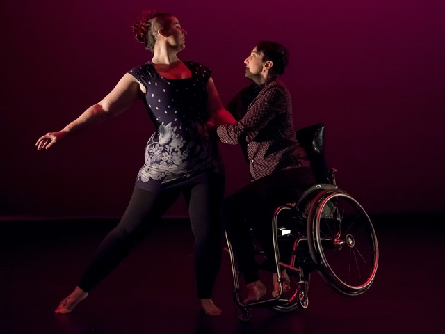 Lindsay and Danielle dance on stage, lit in purple-red light. Lindsay, a white feminine-presenting person in a purple floral dress, stands next to Danielle and extends an arm. Danielle, a masculine-presenting person in purple collared shirt, pulls against Lindsay's arm and waist to draw themselves up onto a one-wheeled tilt in their silver manual wheelchair. The two share an intense look.