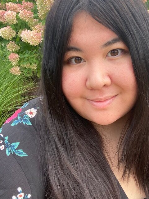 Jess, a Filipino-white person with long straightened black hair and brown eyes, who is slightly smiling at the camera. Jess is wearing a black blouse with flowers on it. There is a bush with flowers in the background.